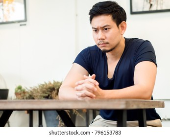 Portrait of serious Asian man sits and thinking in a cafe.