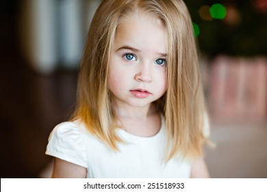Portrait of a serious baby girls blonde with straight hair, close up