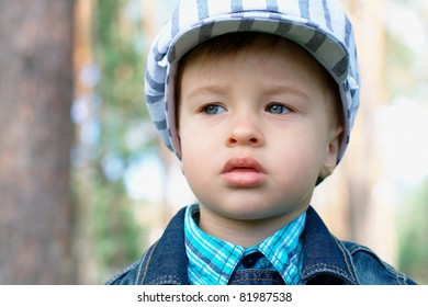 Portrait of a serious baby outdoors with a copy space