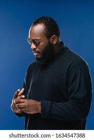Portrait of serious beard African American man with dark sunglasses in studio