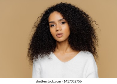 Portrait of serious beautiful dark skinned female with frizzy black hair, has minimal makeup, looks calmly at camera, wears white jumper, stands against brown background, being deep in thoughts.