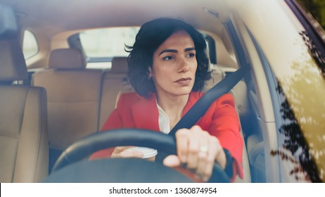 Portrait of Serious Beautiful Young Woman Driving Car through Sunny Suburban Area. Camera Shot Made From the Front Windshield.