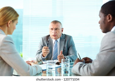 Portrait of serious boss talking to his employees