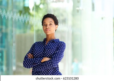 Portrait of serious business woman standing outside building