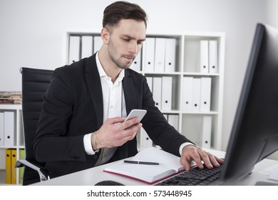 Portrait of a serious businessman holding his cell phone in one hand and typing at his computer keyboard with the second.