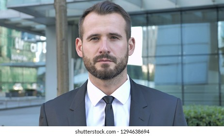 Portrait of Serious Businessman Looking at Camera