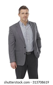 Portrait of serious businessman in shirt and jacket standing with hands in pocket.