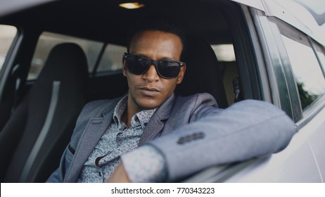 Portrait of serious businessman in sunglasses sitting inside car and looking into camera outdoors