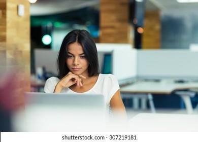 Portret van een serieuze zakenvrouw die laptop op kantoor gebruikt
