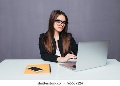 Portrait of a serious businesswoman using laptop in office. Beautiful hipster woman taking notes at modern office