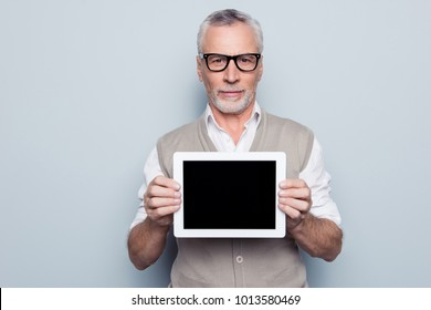 Portrait of serious calm concentrated  virile experienced qualified specialist man beige knitted waistcoat white shirt holding in hands tablet touchpad touchscreen pda isolated on gray background