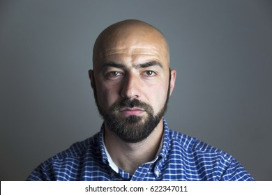 Portrait of serious calm minded man isolated on gray background. Man showing different emotions.