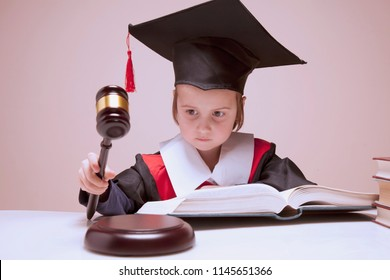 Portrait of serious child girl judge (lawyer) makes a decision. Humorous photo.