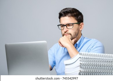 Portrait of serious concentrated man working at laptop and sitting at the table. Isolated on gray