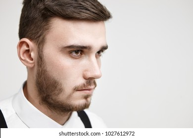 Portrait of serious concentrated young manager with bristle looking ahead of him with focused determined facial expression, ready for hard work. Job, career, competition and challenge concept