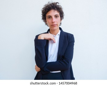 Portrait of serious confident androgynous businesswoman. Young woman in office suit standing for camera with folded arms over studio background. Female business leader concept