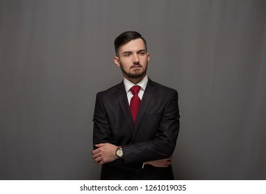 Portrait of serious confident businessman posing against gray background