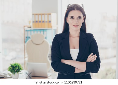 Portrait of serious confident bussines shark holding hands crossed looking at camera standing in modern office