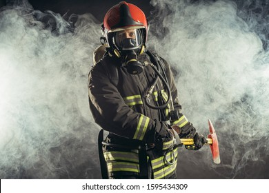 portrait of serious and confident caucasian fireman stand holding hammer, wearing special protective uniform in the smoky background