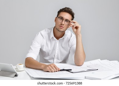 Portrait of serious confident male architect works on blueprint, wears white formal shirt and rounded glasses, uses high internet connection on tablet computer for making drawings. Occupation concept