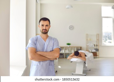 Portrait of serious confident young professional masseur or manual therapist looking at camera standing arms folded against blurred background of his massage room in modern hospital or wellness center