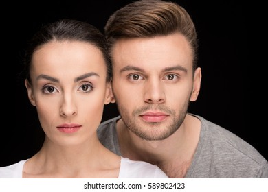 portrait of serious couple looking to camera isolated on black
