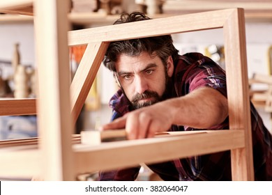 Portrait of a serious craftsman looking focused and serious as he is sanding down a wooden piece that he has manufactured in his woodkwork studio