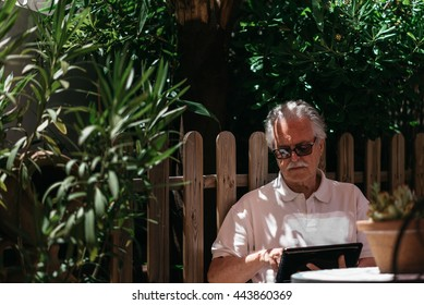 Portrait of serious elderly man in sunglasses in garden using tablet