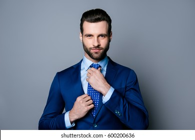 5c59b3911b65 Portrait of serious fashionable handsome man posing in blue suit adjusting  tie