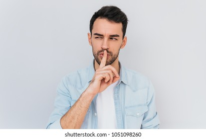 Portrait of serious fashionable male dressed trendy in blue shirt, keeps fore finger on lips, making shh gesture for secret or be quiet. Isolated shot of stylish man shows silence sign. People concept