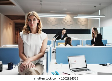 Portrait of serious female employee excluded by colleagues. Blonde businesswoman sitting on desk at work in modern coworking space, looking at camera with sad expression.