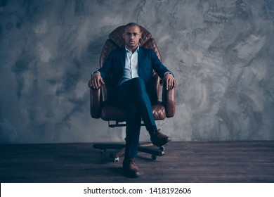 Portrait serious focused chairman boss executive manger cool confident sit brown furniture dream dreamy short hair bald entrepreneur crossed legs wear jackets trousers shoes isolated grey background