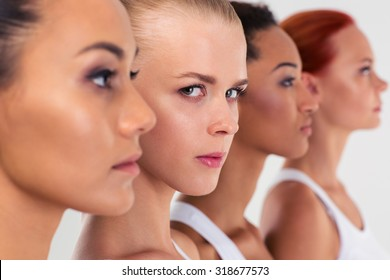 Portrait of a serious four woman standing in a row  - Shutterstock ID 318677573