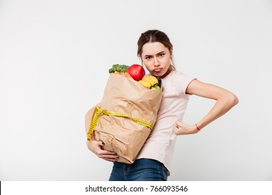 Portrait of a serious girl holding bag with groceries isolated over white background