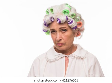Portrait of serious grandmother with rollers on in studio. Beautiful senior lady posing for photographer.