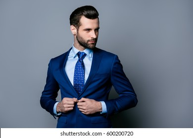 Portrait of serious handsome man in blue suit and tie buttoning jacket