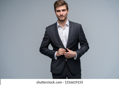 Portrait of serious handsome man in gray suit buttoning jacket against gray background.