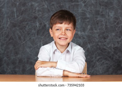 Portrait of serious happy little schoolchild on background of backboard in school, indoor.