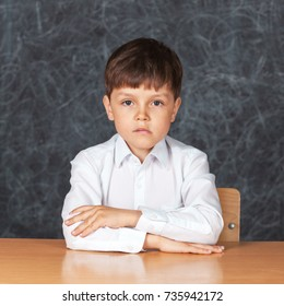 Portrait of serious happy little schoolchild on background of backboard in school, indoor.