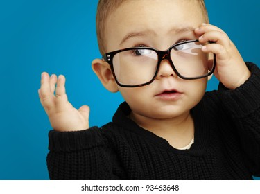 portrait of serious kid wearing glasses and doing a gesture over blue background