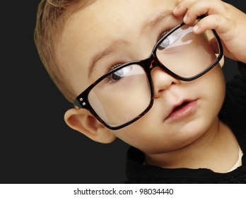 portrait of serious kid wearing glasses and doing a gesture over