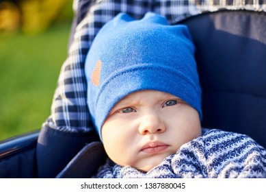 Portrait of a serious little boy in a blue cap sitting in a pram outdoors