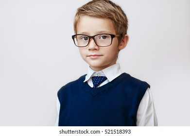 Portrait of a serious little boy in spectacles and vest.