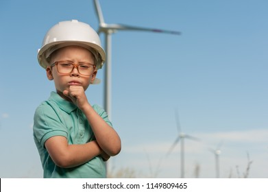 Portrait of a serious little cute boy in a green shirt and a white helmet standing in front of windmills. Little boy dreams of becoming a power engineer