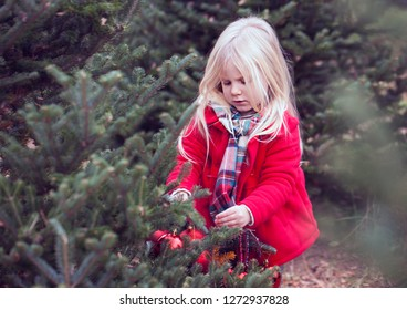Portrait of serious little girl decorating fir trees outdoors. Girl hanging baubles at farm