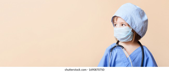 Portrait of serious little girl dressed up in doctor holds on hands baby doll on isolated background /concept  pediatric emergency/obstetrics/abortion protest/artificial insemination