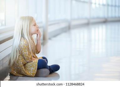 Portrait of serious little girl sitting on floor kissing hand