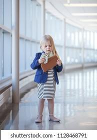 Portrait of serious little girl taking money off wallet