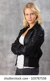 Portrait of a serious looking modern blonde woman, with crossed arms looking at the camera. Studio shot against a gray background.