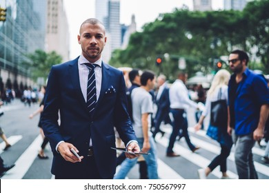 Portrait of serious male entrepreneur standing on crosswalk in new york city looking at camera, confident businessman dressed in elegant suit using modern technology while walking in megapolis